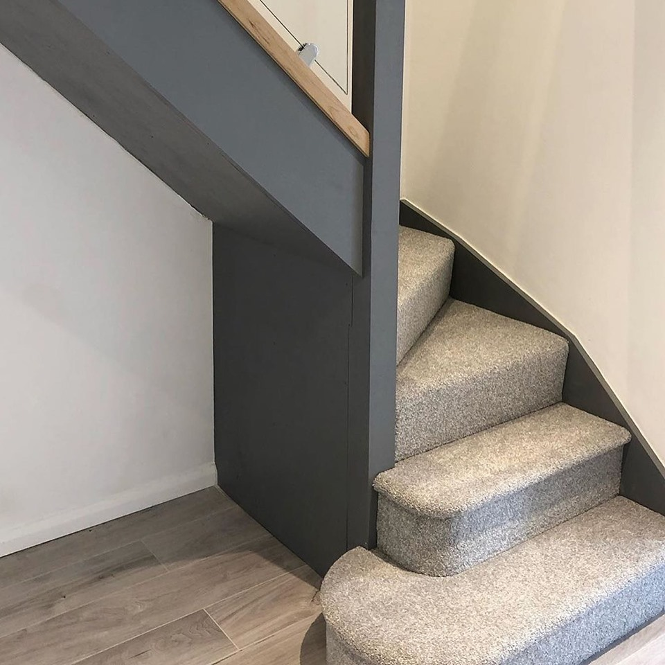 Close up shot of the foot of a winder staircase painted and carpeted in grey