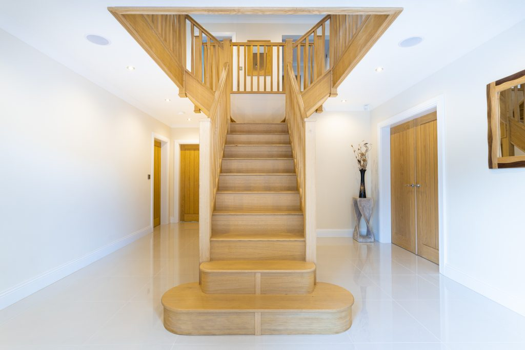 Large hallway with T-shaped oak staircase leading up to a landing