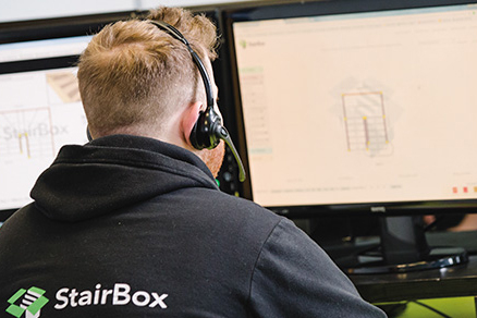 A man in a StairBox branded hoody has his back to the camera as he is facing two computer screens with a staircase design on screen. He is wearing a phone headset