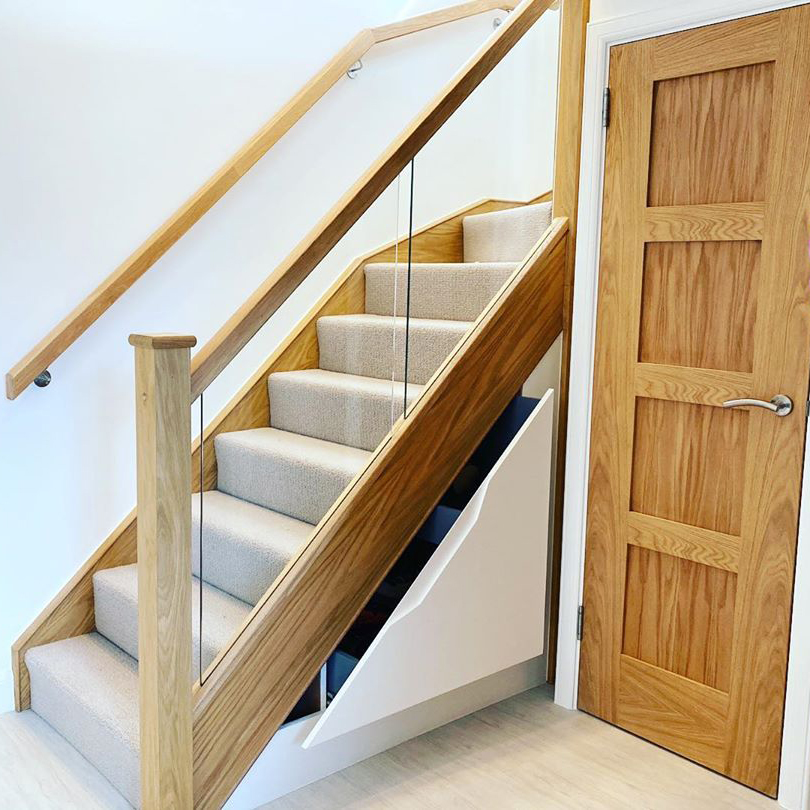 A carpeted staircase with oak details has a triangular shaped door built into the space underneath. There is a right hand turn in the flight, meaning there is also space for a full height door and cupboard.