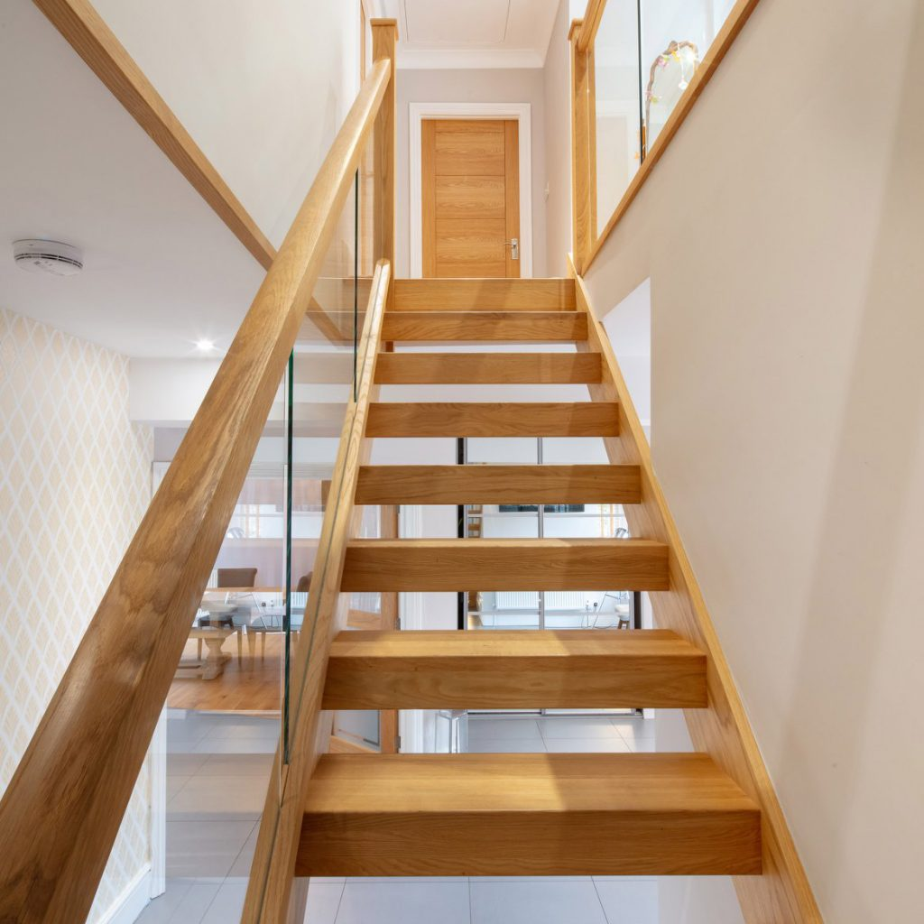 Looking up an oak staircase that has open risers and embedded glass balustrades. An oak door is just visible on the landing at the top of the flight.