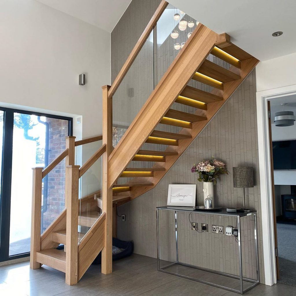 An open plan oak staircase with embedded glass balustrades. The staircase has a righthand turn and the under side is visible. Each riser has an LED lighting strip mounted on the under side, giving a warm glow